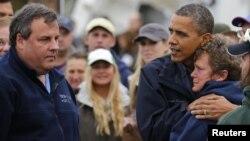 Presiden Barack Obama (kanan), bersama Gubernur Chris Christie (kiri) berusaha menghibur seorang warga di New Jersey yang rumahnya porak-poranda akibat badai Sandy (31/10).