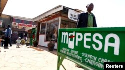 FILE - A man walks away from a retail mobile money transfer shop in Ngong township on the outskirts of Kenya's capital Nairobi.