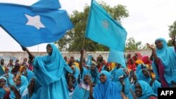 Somali women wave their national flag at Konis stadium, in Mogadishu, during a ceremony marking the anniversary of Somalia's independence, July 1, 2012.