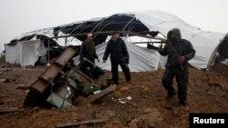 Các nhân viên thuộc lực lượng an ninh Palestine trung thành với nhóm Hamas kiểm tra những thiệt hại sau khi Israel oanh kích đường hầm chuyển hàng lậu ở Rafah, mạn nam Dải Gaza, 13/3/14