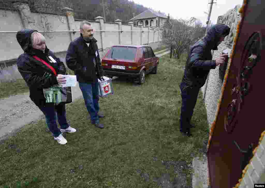 Election officials arrive with a mobile ballot box at a house during voting in a referendum in the village of Pionerskoye, Crimea, Ukraine, March 16, 2014.