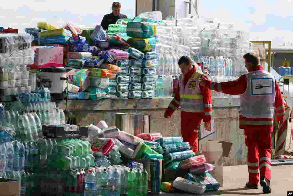 ریڈ کراس کے اہلکار پناہ گزینوں کے لیے امدادی سامان کا معائنہ کر رہے ہیں۔