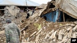People walk around a destroyed house in Karakocan province of southeastern city Elazig, 08 Mar 2010