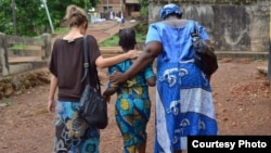 Cora, a trafficking survivor, walks with her case manager and social worker in Sierra Leone. (Credit: Women's Health Initiative)