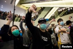 FILE - Protesters give thumbs-down signs to mainland Chinese travellers during a demonstration inside a shopping mall in Hong Kong, Feb. 15, 2015.