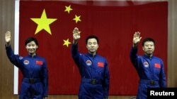 Chinese astronauts Jing Haipeng (C), Liu Wang (R) and Liu Yang, China's first female astronaut, wave to the media during a news conference at Jiuquan Satellite Launch Center, in northwest China's Gansu province, June 15, 2012.