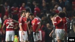 Marouane Fellaini de Manchester United, à droite, Anthony Martial, au centre-droite, Antonio Valencia, à gauche, et Matteo Darmian, au centre-gauche, se parlent à la fin de la du match de football de la ligue d'Europe entre Manchester United et Liverpool,