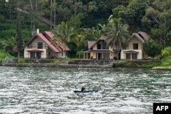 Seorang nelayan mendayung melewati hotel-hotel resor di pulau Samosir, Danau Toba, 3 April 2019. (Foto: dok).