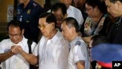 Senator Filipina Juan Ponce Enrile (kedua dari kiri) dibantu menuruni tangga menuju ambulan setelah mengikuti penyidikan di kantor polisi Filipina terkait tuduhan penggelapan.