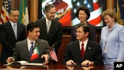 FILE - Mexican Foreign Affairs Undersecretary for North America Geronimo Gutierrez (front left) and Assistant Secretary of Labor for Occupational Safety and Health John Henshaw (front right) pause as they sign a workplace safety agreement, July 21, 2004, in Washington.