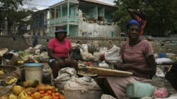 Women sell fruits and vegetables in front of a damaged house in Jacmel, Haiti.