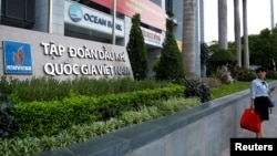A woman stands in front of a branch of Ocean Bank located at the Petro Vietnam's building in Hanoi