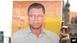 周一在孟买举行示威的新闻记者举着被害记者戴伊的照片