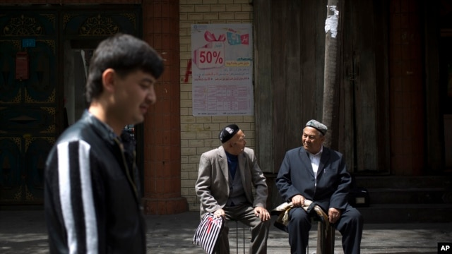 FILE - Ethnic Uighurs chat in an alley before they proceed for their Friday prayers near a mosque in Urumqi, China's northwestern region of Xinjiang.