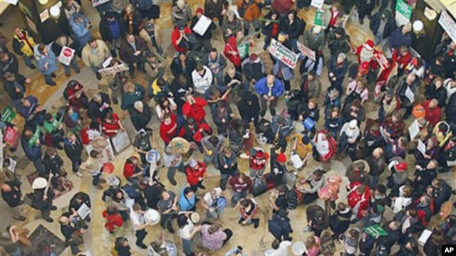 Demonstrators bang drums and chant inside the state Capitol during the eighth day of protesting against Governor Scott Walker's bill to eliminate collective bargaining rights for many state workers,  in Madison, Wis., February 22, 2011
