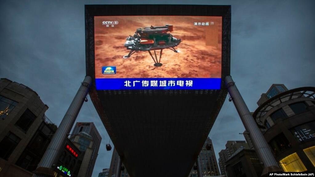 北京街头一家商场的大屏幕正在播放中国官媒报道中国火星探测器天问一号成功登陆火星的视频。(2021年5月15日)(photo:VOA)