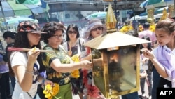 FILE - Women light incense sticks before offering prayers at the reopened Erawan Shrine, the popular tourist site where 20 people were killed on August 17 in a bomb blast in Bangkok, Aug. 20, 2015.