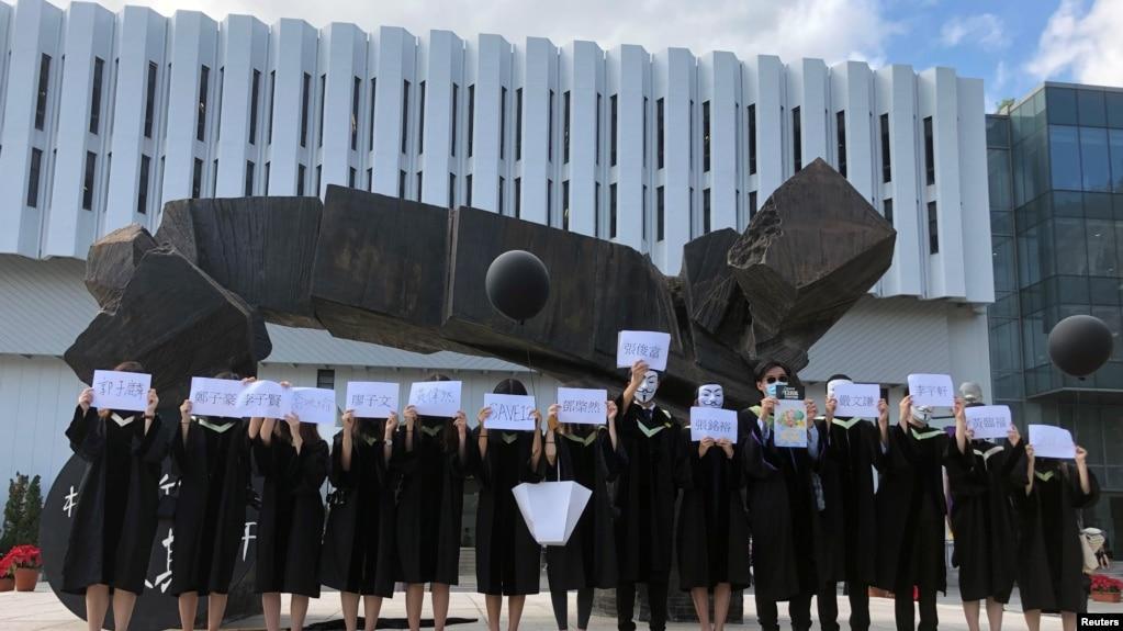 香港中文大学毕业生举起被中国拘押的12名港人的姓名牌子。(2020年11月19日)(photo:VOA)