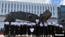 香港中文大学毕业生举起被中国拘押的12名港人的姓名牌子。(2020年11月19日)