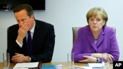 British Prime Minister David Cameron and German Chancellor Angela Merkel meet on sidelines of EU summit, Brussels, Oct. 25, 2013.