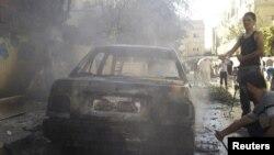 Cư dân khu vực al-Saad đứng cạnh một chiếc xe bị hư hại sau vụ pháo kích do quân đội chính phủ Syria thực hiện, ngày 3/11/2012