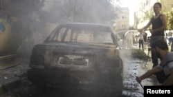Residents stand next to a damaged car after shelling by forces loyal to Syria's President Bashar al-Assad at al-Saad near Deraa, November 3, 2012.