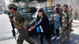 Lebanese army special forces soldiers assist teachers as they flee their school after deadly clashes erupted nearby along a former 1975-90 civil war front-line between Muslim Shiite and Christian areas at Ain el-Remaneh neighborhood, in Beirut, Lebanon.