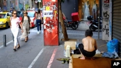 Pedestrians pass by a homeless man in the Monastiraki area of central Athens, Greece, June 24, 2015.