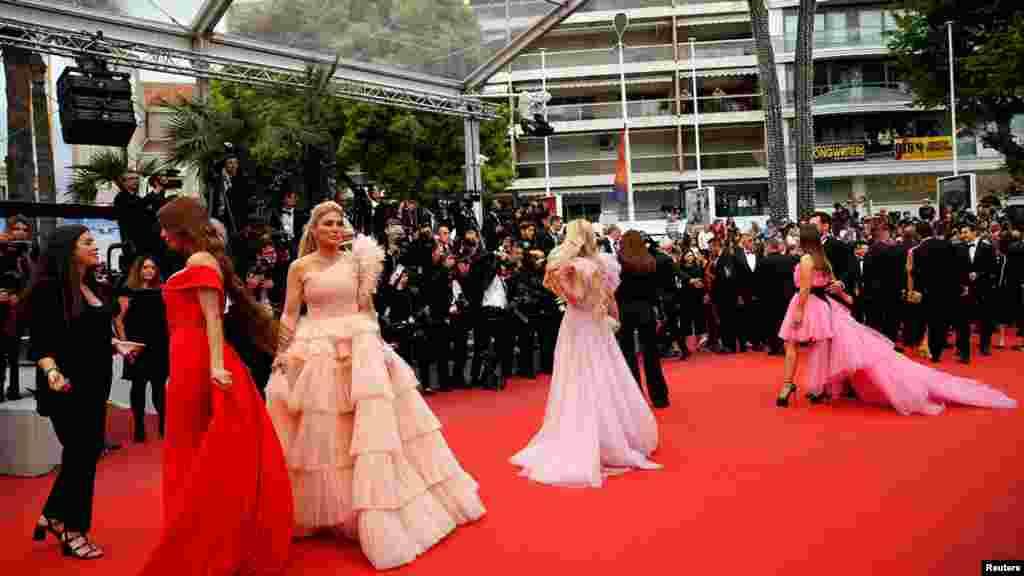 خواتین اداکارائیں ریڈ کارپٹ پر فوٹوگرافرز کو پوز دے رہی ہیں