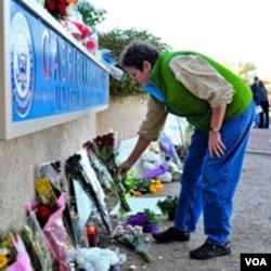 Seorang perempuan meletakkan bunga di luar kantor anggota Kongres Gabrielle Giffords di kota Tucson, Arizona.