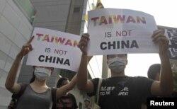 """示威者在台北抗议习马会,他们手持标语""""台湾不是中国""""(2015年11月7日)"""
