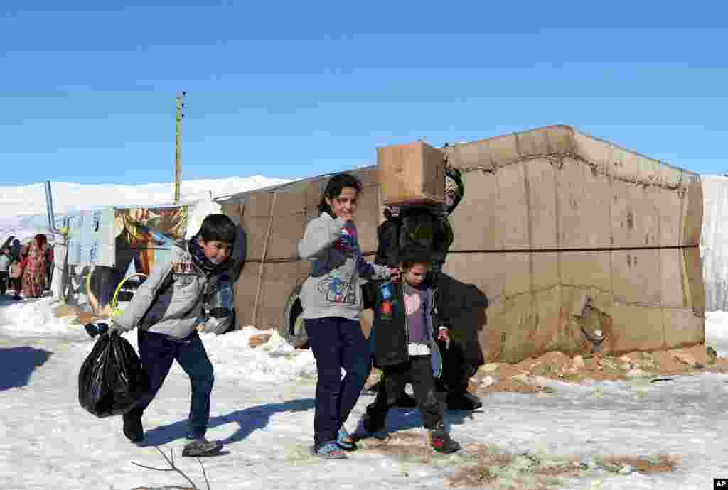 Syrian refugees carry aid donated by the local municipality near the ancient Roman city of Baalbek in eastern Lebanon, Dec. 15, 2013.