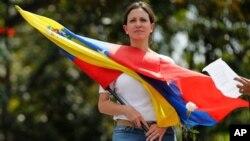 La diputada opositora María Corina Machado con una bandera venezolana durante una manifestación en Caracas.