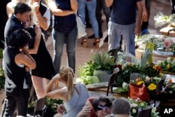 Italian Premier Matteo Renzi, left, comforts a woman at the end of the state funeral service for some of the victims of the earthquake that hit central Italy last Wednesday, in Ascoli Piceno, Italy, Aug. 27, 2016.