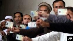 Avganistanci polazuju lična dokumenta dok čekaju da obave glasanje na jednom od biračkih mesta u Kabulu