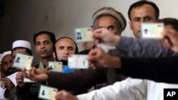 阿富汗人等待投票的时候出示身份证