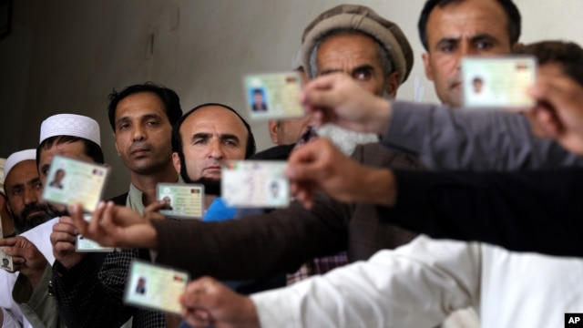 Afghan men display their identification cards as the wait to cast their votes outside a polling station in Kabul, Afghanistan, Saturday, June 14, 2014.