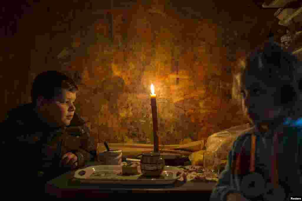 Lazar and his sister Andjelka sit by a candle in their home in the eastern Serbian town of Majdanpek. Electricity workers in Serbia struggled through snow, ice and treacherous terrain to restore electricity to an eastern town left shivering without power, heating or running water for a fourth day.