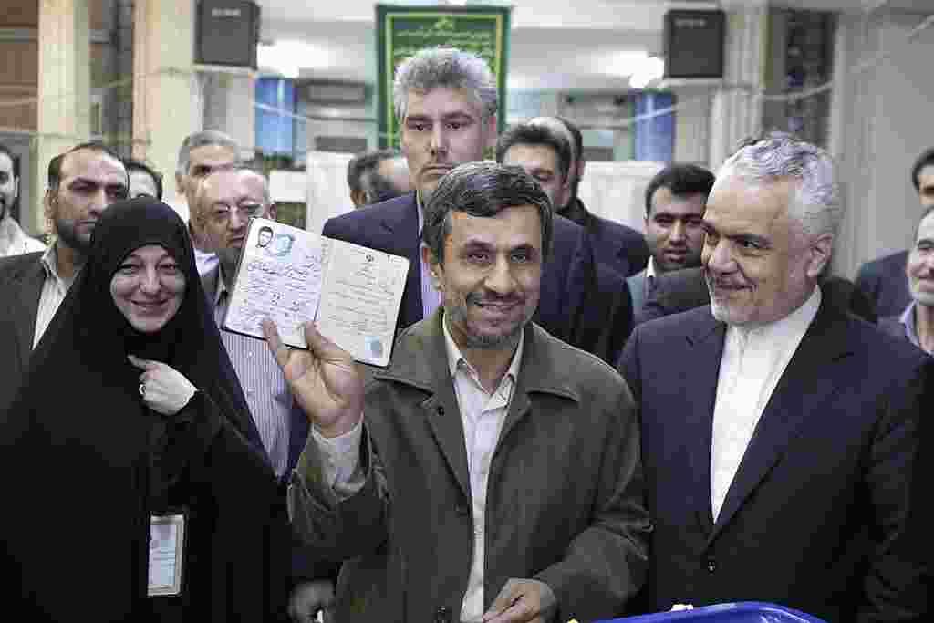 El presidente iraní Mahmoud Ahmadinejad muestra su documento de identidad tras votar en Teherán, acompañado por el vicepresidente, Mohammad Reza Rahimi, a su derecha.