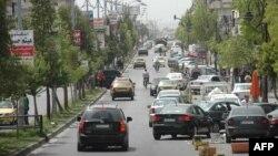 Những chiếc xe chạy trên đường của thành phố Homs đang bị vây hãm.