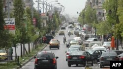 Cars drive on a street in a government-controlled district of Homs, May 7, 2014.