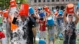 Boston City Councillor Tito Jackson, left in suit, leads some 200 people in the ice bucket challenge at Boston's Copley Square, Thursday, Aug. 7, 2014.