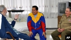 FILE - In this June 17, 2011 photo released by Granma newspaper, Cuba's former President Fidel Castro, left, and brother, Cuba's President Raul Castro, right, speak with Venezuela's President Hugo Chavez at a hospital as Chavez recuperates from surgery in