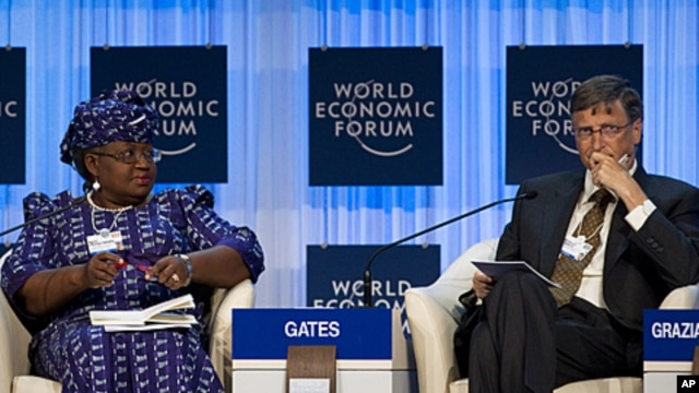 Bill Gates, right, and Nigerian Finance Minister Ngozi Okonjo-Iweala attend a panel session at the World Economic Forum in Davos, January 26, 2012.