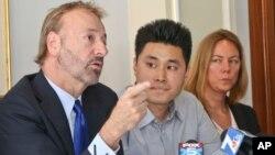 亚裔学生丹尼尔·钟(中)的律师(左)在记者会上讲话(2014年7月10日)