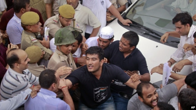 Police try to remove supporters of veteran Indian social activist Anna Hazare who were attempting to block the vehicle carrying Hazare after he was arrested by police in New Delhi, Aug. 16, 2011.