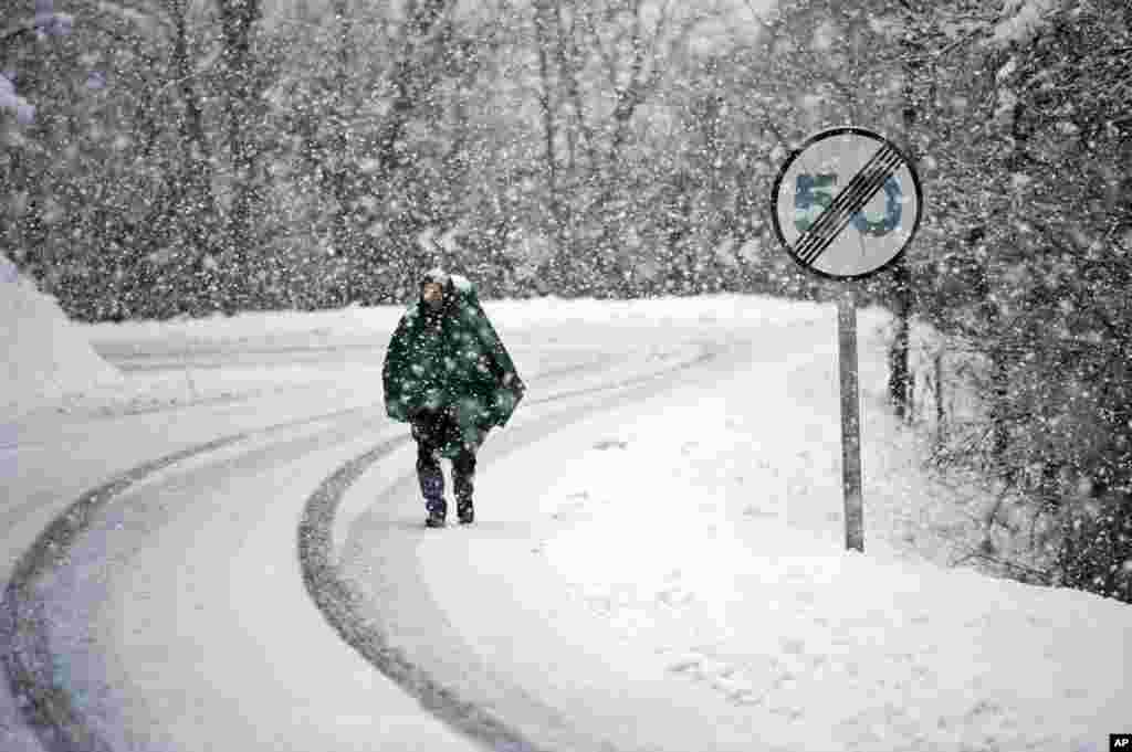 Antonio Lazza, a 60 year old pilgrim from Italy, walks alongside the road of Saint James's Way during a snow fall on a Spring morning near the Pyrenees town of Erro, northern Spain. The Saint James Way is a pilgrimage route ending in Santiago de Compostela that attracts people from all over the World.