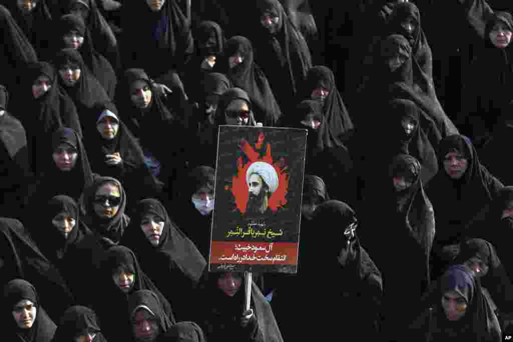 An Iranian woman in Tehran holds up a poster showing Sheikh Nimr al-Nimr, a prominent Shi'ite cleric who was executed last week by Saudi Arabia. Allies of Saudi Arabia followed the kingdom's lead and began scaling back diplomatic ties to Iran after the ransacking of Saudi diplomatic missions in the Islamic Republic, violence sparked by the Saudi execution of al-Nimr.
