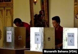 Gubernur DIY Sultan Hamengkubuwono X (kiri) dan permaisuri GKR Hemas (kanan) sedang melakukan pencoblosan di PTS 15 Kelurahan Panembahan, Kecamatan Kraton Yogyakarta, Rabu (17/4). (Foto: VOA/Munarsih Sahana).