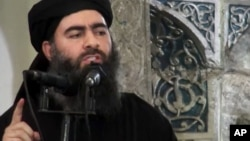 FILE - This image taken from a militant website July 5, 2014, purports to show the leader of the Islamic State group, Abu Bakr al-Baghdadi, who released a new message late Wednesday, encouraging his followers to keep up the fight for the city of Mosul.